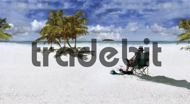 Man wearing sun hat sitting on a chair on a beach in the Caribbean at Punta Allen, Mexico, North America
