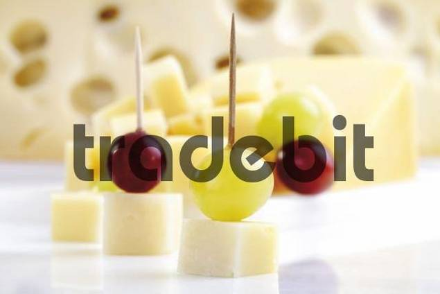 Diced cheese with grapes, half a cheese wheel in background
