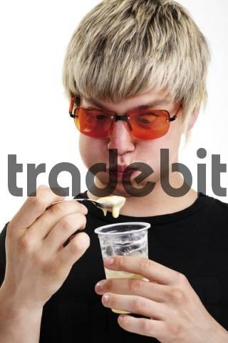 Young man wearing sunglasses eating yogurt
