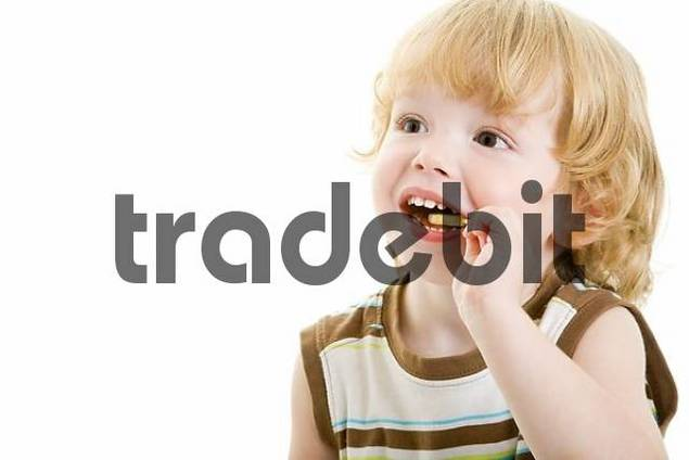 Three-year-old boy licking a yellow lollipop