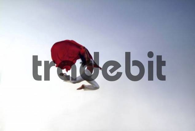 Woman jumping into the air, trailing red cloth: free, carefree, independent