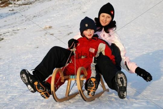 Mother and son tobogganing