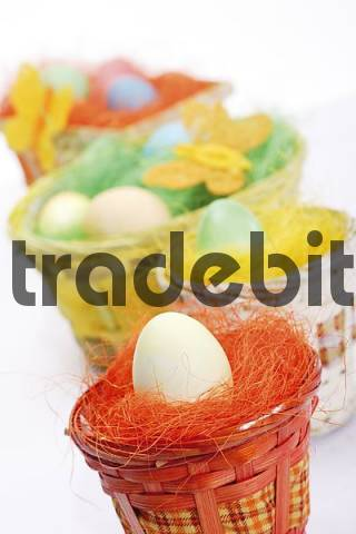 Pastel-coloured Easter egg in nests with butterfly decorations