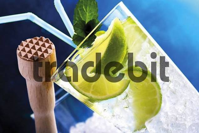 Caipirinha with crushed ice, wooden pounder and straws