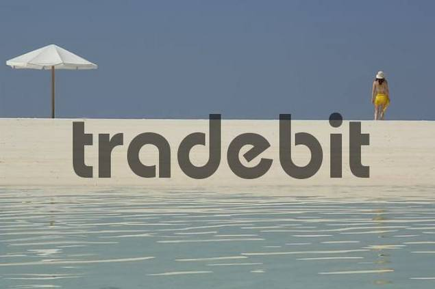 Woman and parasol on the beach, Diffushi Island, Holiday Island, Southern Ari Atoll, Maldives, Indian Ocean