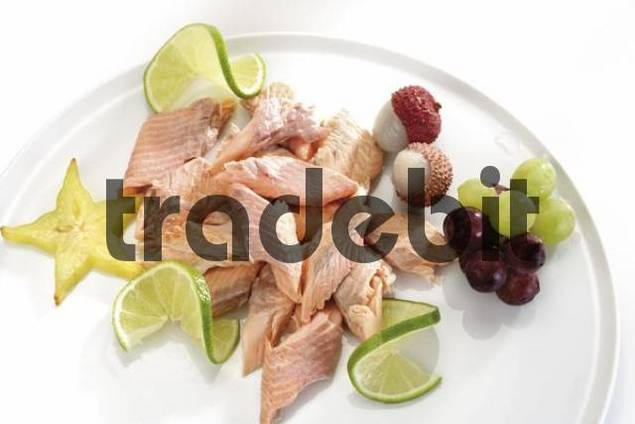 Salmon garnished with fruit: star fruit carambola, limes, grapes and lychees