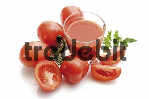 Glass of tomato juice surrounded by plum tomatoes, Heirloom Tomato variety Lycopersicon esculentum
