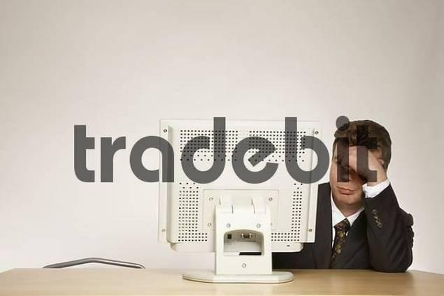 Businessman sitting in front computer, despairing