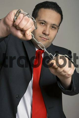 Businessman holding chain, ready to tear in apart, tension