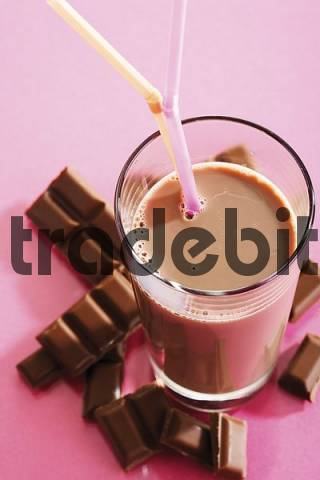 Glass of chocolate milk and chocolate bar pieces