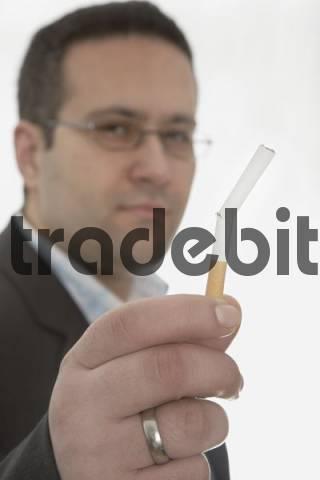 Man holding broken cigarette: smoking cessation