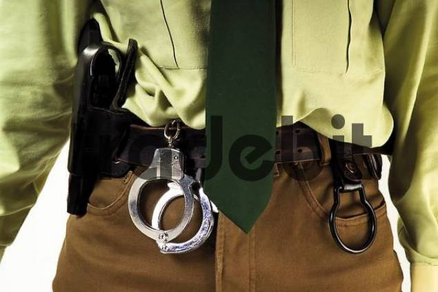 Detail, female police officer with handcuffs and gun holster