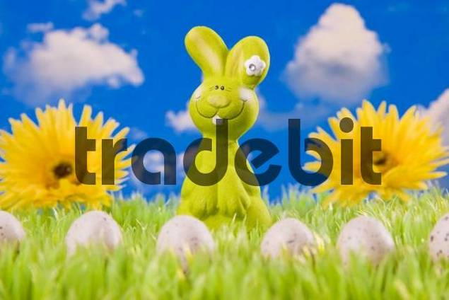 Easter bunny on meadow with Easter eggs in front of a blue cloudy sky
