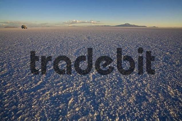 Salt lake Salar de Uyuni with car at sunrise, Altiplano, Bolivia, South America