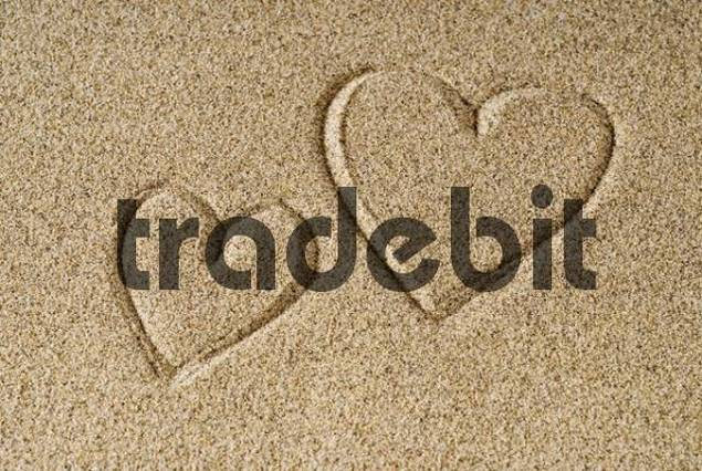 Two hearts drawn into beach sand
