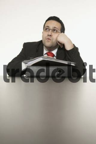 Businessman sitting at desk, whistling
