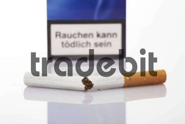 Cigarette broken in half, cigarette pack in background