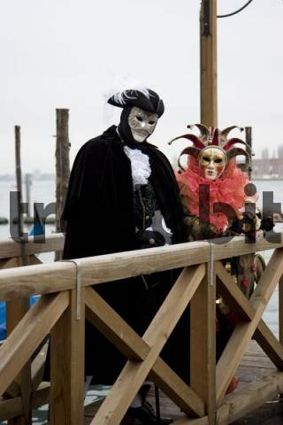 People wearing black-and-white and red costumes and masks standing on a dock, Carnevale di Venezia, Carneval in Venice, Italy