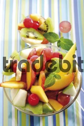 Fruit salad: kiwis, bananas, apples, peaches, mangoes, grapes and maraschino cherries