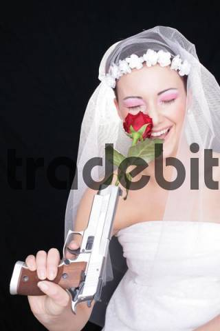 Bride laughing as she totes a gun and a rose