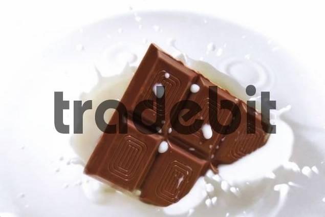 Chocolate falling into milk