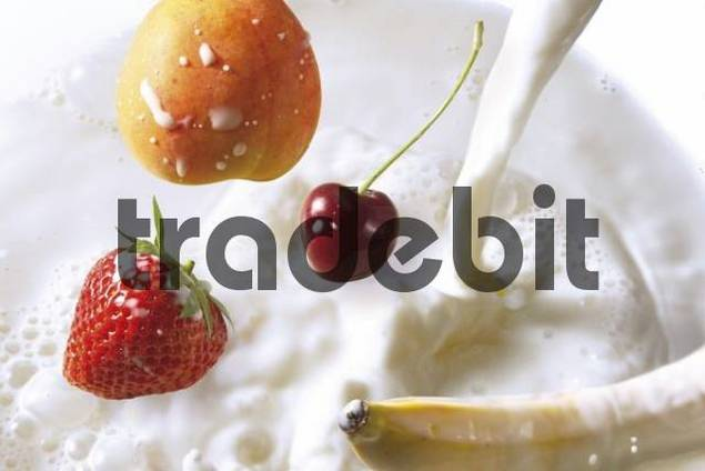 Fruit falling into milk - strawberry, cherry, banana and peach