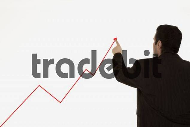 Businessman pointing at rising stock prices
