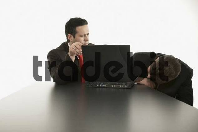Two businessmen sitting in front of a laptop, looking for a solution