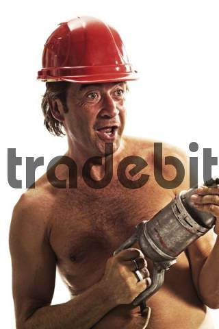 Shirtless construction worker wearing a construction helmet, handling a drill
