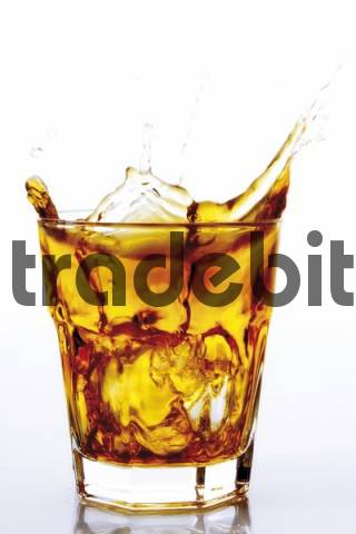 Ice cube falling into a glass of whiskey