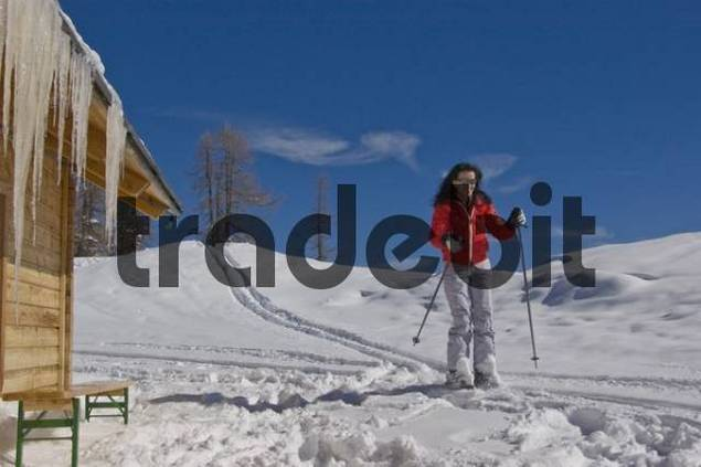 Woman skiing past icicles hanging from a cabin in Hinterstoder, Austria, Europe