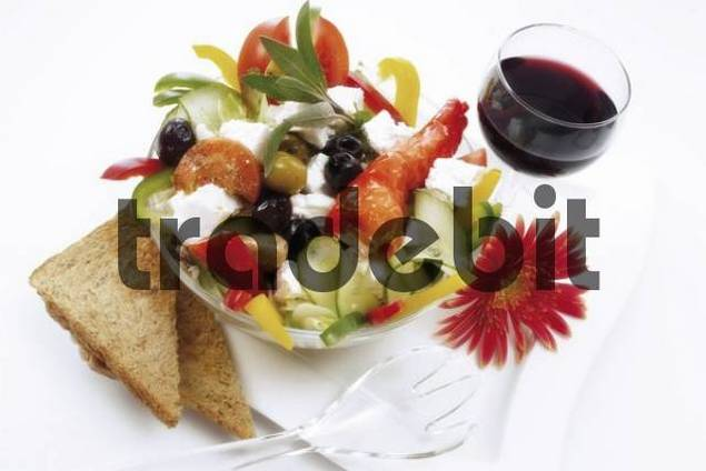 Fresh feta salad and a glass of red wine: Greek feta cheese, black and green olives, colourful capsicum stripes, cucumber, tomato wedges and hot peppers