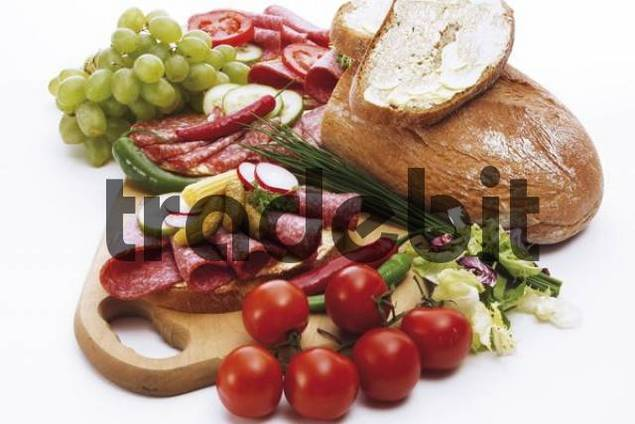 Midday snack on a cutting board: salami sandwiches with hot peppers, pickles, cucumbers and radishes, garnished with tomatoes, grapes and half a loaf of bread