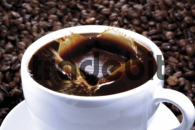 Piece of chocolate falling into a cup of coffee