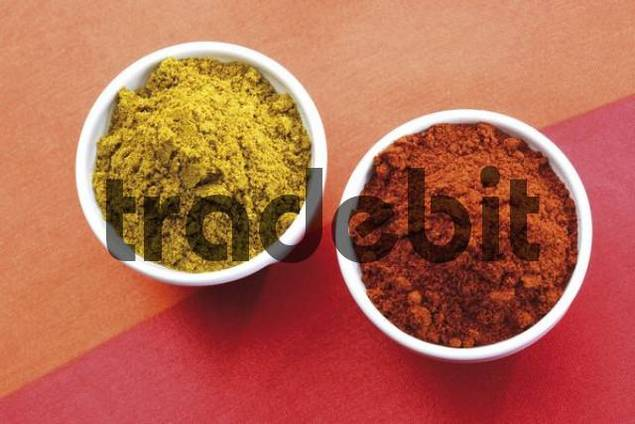 Small bowls of curry powder and paprika