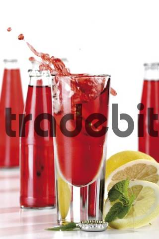 Italian herbal liqueur spilling out of a glass, similar to Campari