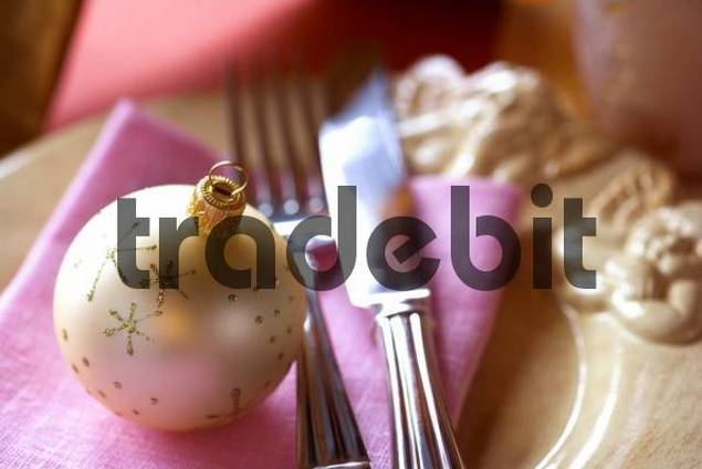 Christmas ornament on a plate together with a napkin and cutlery