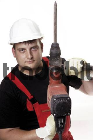 Construction worker wearing a white hardhat holding a jackhammer in his hands