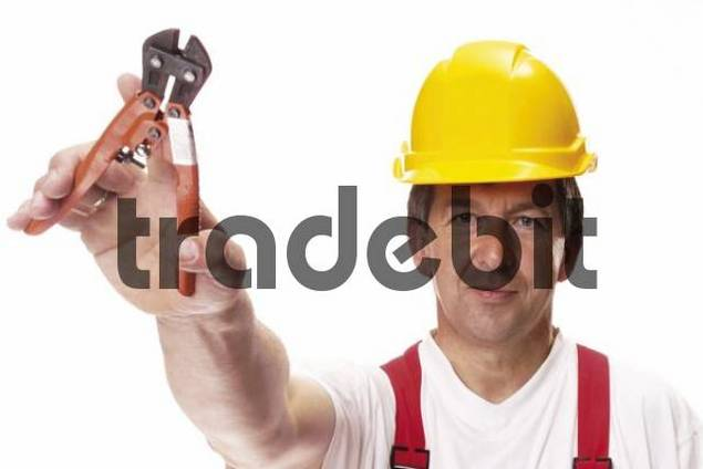 Construction worker wearing yellow hardhat holding pliers
