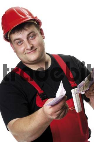 Construction worker wearing red hardhat getting paid
