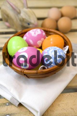 Hand-painted Easter eggs in a brown bamboo bowl beside a wooden Easter bunny