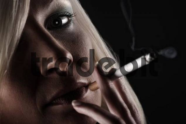 Portrait of a young blonde woman smoking a cigarette