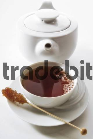 Cup of black tea in front of a teapot