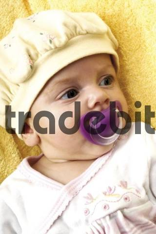 Baby wearing a hat with a soother in its mouth