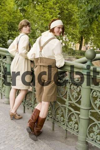 Two young women wearing 1920s-style designer clothes standing at the railing of the Admiralsbruecke Admiral Bridge in Berlin, Germany, Europe