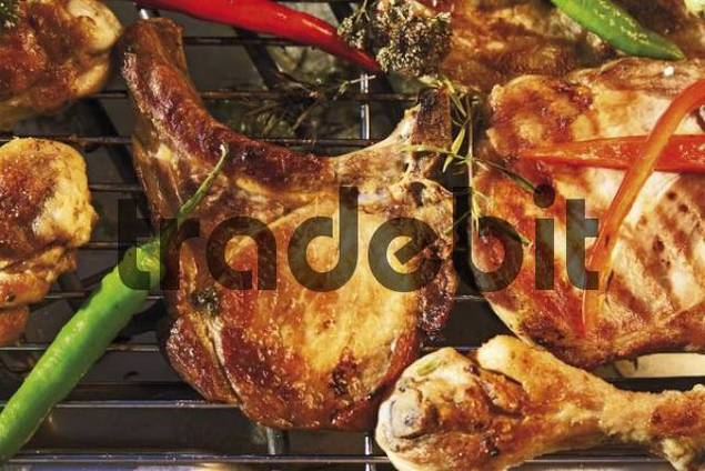 Ourdoor barbecue with barbecue meat - chop, cutlet, drumstick, capsicum and herbs