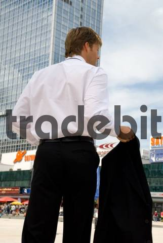 Young businessman on the street holding jacket