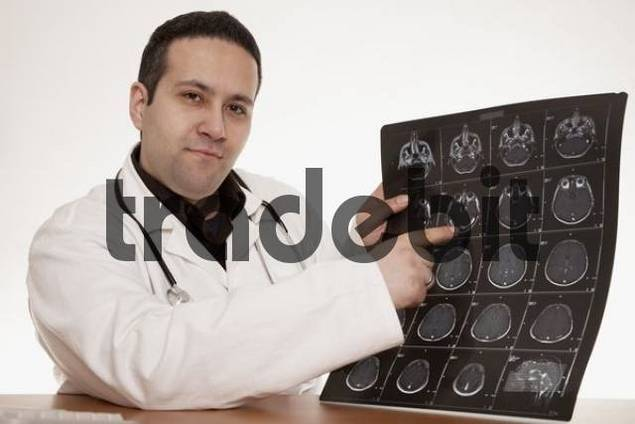 Physician with stethoscope pointing to a CT scan image of a skull