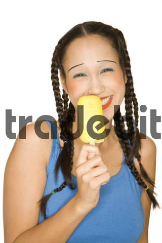 Portrait of young woman of Philippine origin, with girlie make-up, holding a popsicle