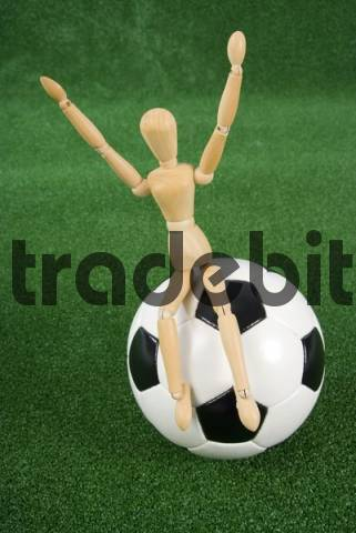 Symbolic shot, football fan: jointed mannequin sitting on a football cheering